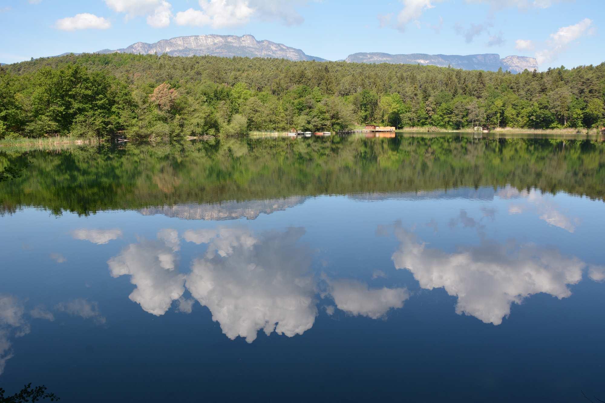 Die Wolken spiegeln sich auf der spiegelglatten Oberfläche im Montiggler See. Hinten sind die Berge zu sehen.